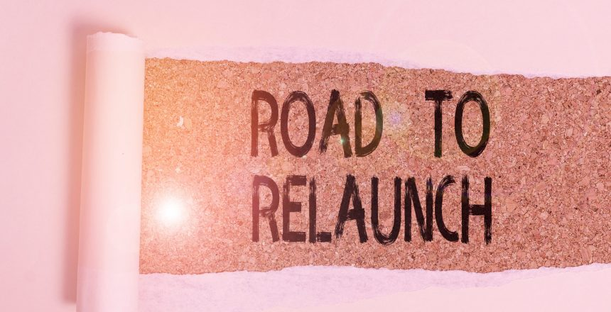 Conceptual hand writing showing Road To Relaunch. Concept meaning In the way to launch again Fresh new start Beginning Cardboard which is torn placed above a wooden classic table